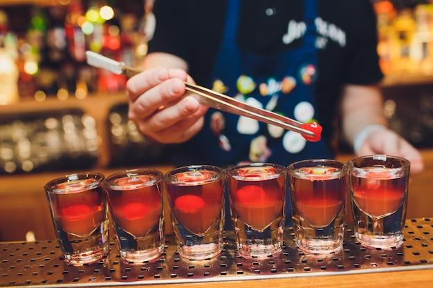 Barkeeper mann macht heiße alkoholschüsse auf der bar in der kneipe mit einem professionellen brenner. der barkeeper zündet ein feuerzeug über einem glas an. entspannen sie sich im nachtclub. heiße feuergetränke. lässt die party.