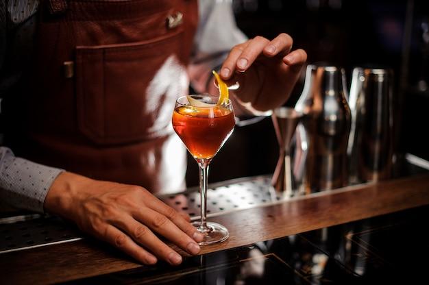 Barkeeper mit glas und zitronenschale bereiten cocktail an der bar vor