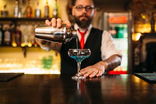 Barkeeper mit shaker, der alkoholcocktail macht