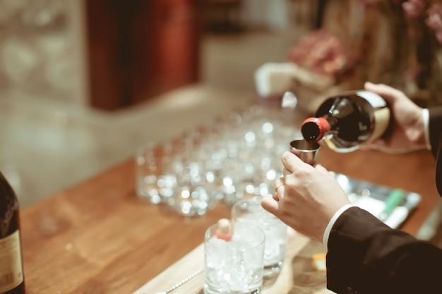 Barkeeper pour cocktails zutaten in messbecher für die herstellung von cocktails