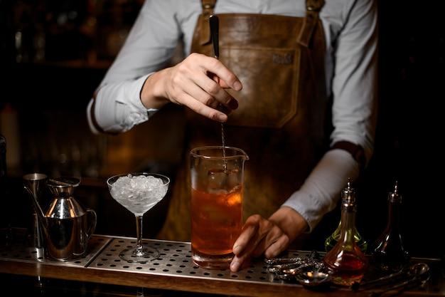 Barkeeper rührt einen leckeren cocktail in die messglasschale
