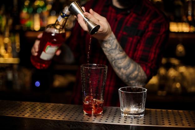 Barkeeper schenkt getränke ein und macht einen fremdenlegion-cocktail vom stahl-jigger bis zum glasmessbecher auf der bartheke