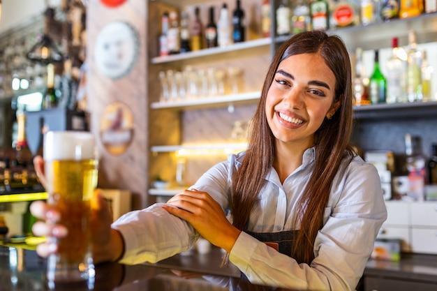 Barkeeper serviert ein gezapftes bier an der theke, regale voller flaschen mit alkohol im hintergrund
