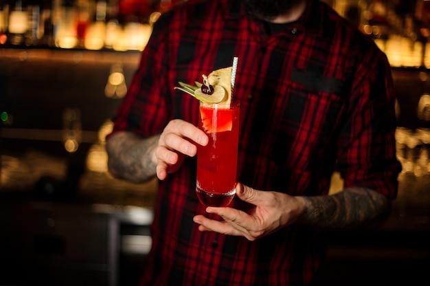 Barkeeper serviert ein glas hurricane punch cocktail mit limette und getrockneter ananas auf der theke