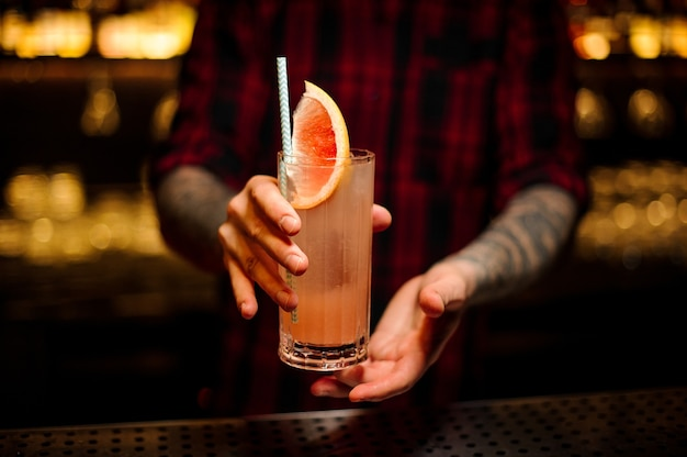 Barkeeper serviert ein glas köstlichen cocktails mit grapefruit an der bartheke