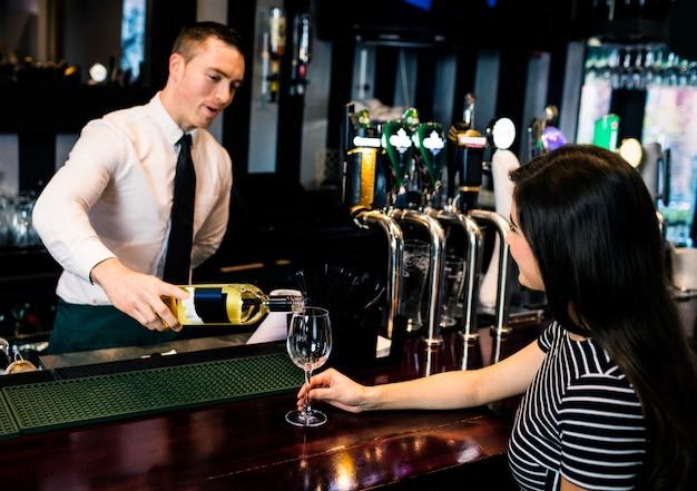 Barkeeper serviert ein glas wein in einer bar