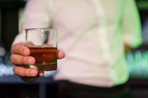 Barkeeper serviert ein glas whisky in der bar