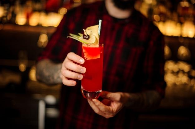 Barkeeper serviert einen hurricane punch cocktail mit limette und getrockneter ananas auf der theke