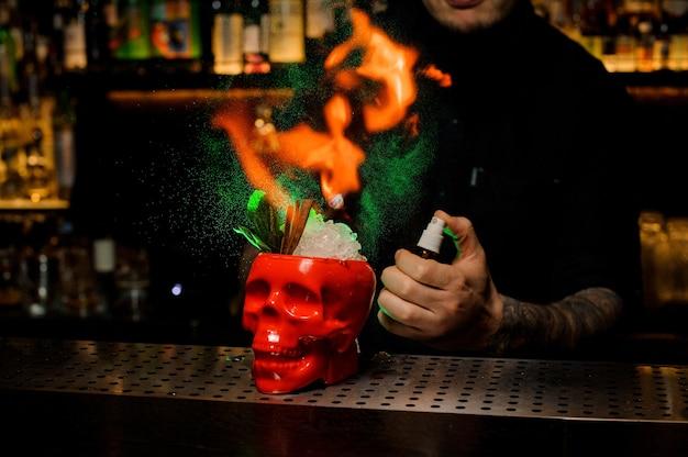 Barkeeper sprüht den leckeren cocktail in der schädeltasse aus dem speziellen vaporizer auf und flammt ihn auf der bartheke auf