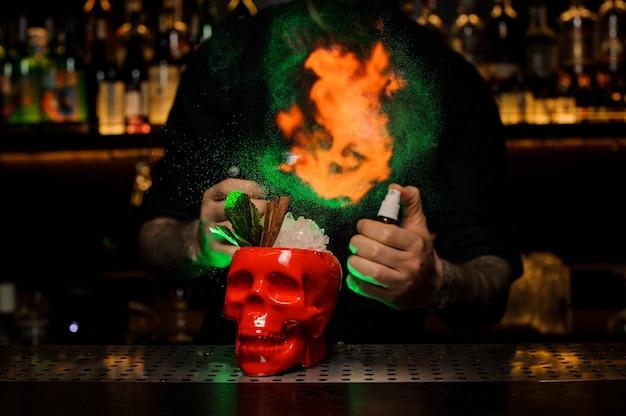 Barkeeper sprüht den leckeren cocktail in der schädeltasse aus dem speziellen vaporizer ins grüne und feuert ihn auf die bartheke.