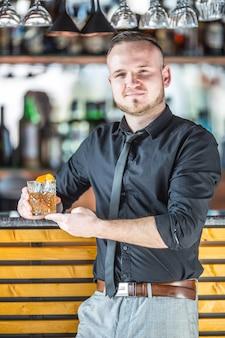 Barkeeper steht vor der bar und hält cocktailgetränk in der hand.