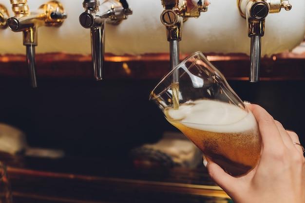 Barkeeper zieht ein pint bier hinter die bar.