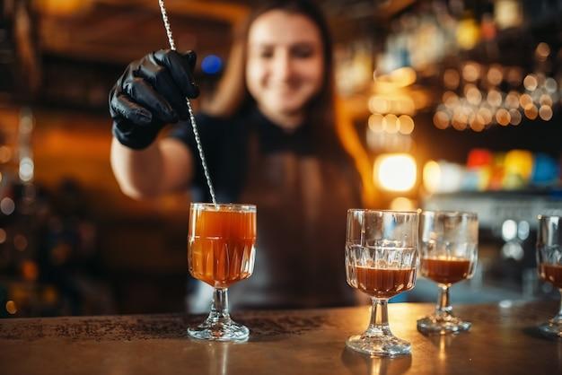 Barkeeperin, die an der bartheke einen cocktail macht