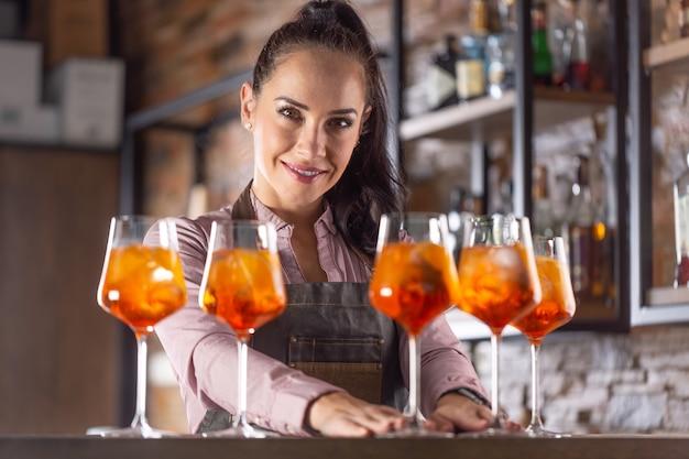 Barmaid bietet aperol-spritz-cocktails an einer bar an, die in die kamera lächelt.