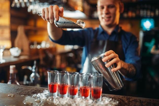 Barmann an der theke mit gläsern, die im eis stehen