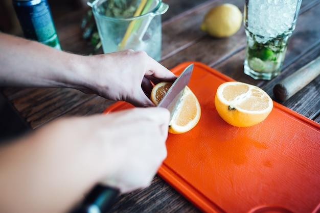 Barmann bereitet fruchtalkoholcocktail auf basis von limette, minze, orange, soda und alkohol zu
