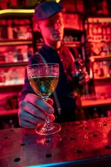 Barmann, der den gästen in buntem neonlicht alkoholische cocktails, shots und getränke vorschlägt