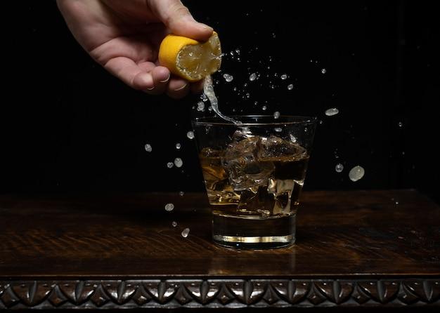 Barmann, der den zitronensaft in den cocktail auf dem schwarzen drückt