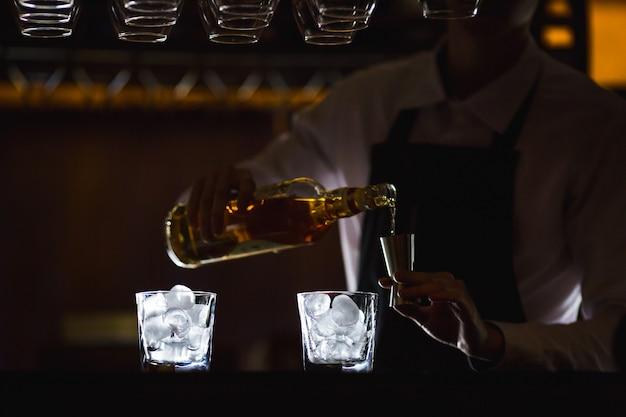 Barmann, der einen alkoholfreien cocktail in einem restaurant zubereitet.