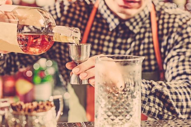 Barmann, der einen alkoholischen cocktail an der bartheke an der bar macht