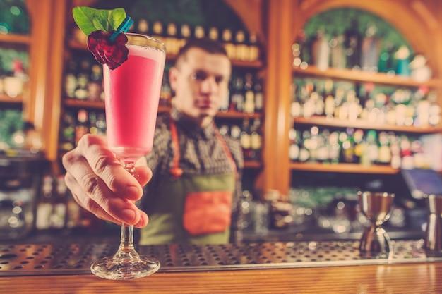 Barmann, der einen alkoholischen cocktail an der theke an der bar anbietet