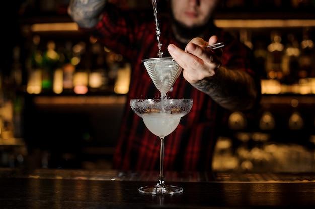 Barmann, der frischen margarita-cocktail in ein cocktailglas gießt