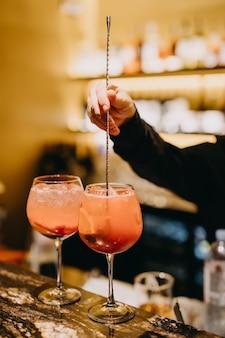 Barmann, der longdrink-cocktails in einem restaurant am bartheke macht.