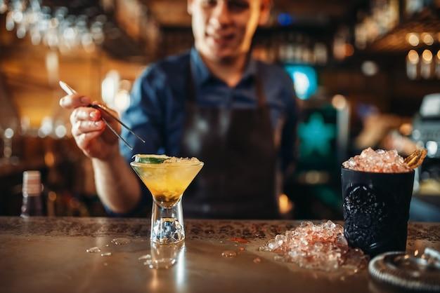 Barmann, der mit hilfe einer pinzette coctail macht