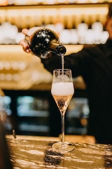 Barmann, der rosenchampagner in ein glas auf einer bartheke gießt.