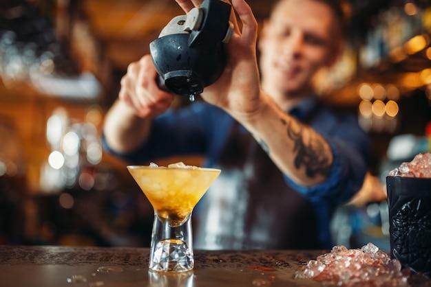 Barmann drückt zitrone in das glas voller eis