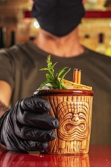 Barmann gibt tiki cocktail an der bar.