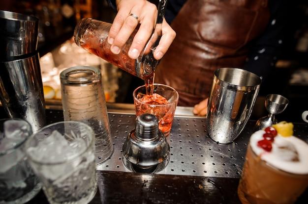 Barmann gießt aus einem shaker einen alkoholischen cocktail in ein kristallglas