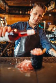 Barmann gießt getränke in das glas voller eis