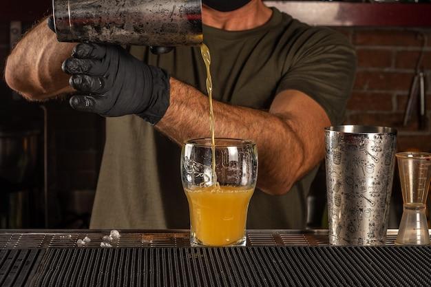 Barmann in der bar gießt orangenalkoholcocktail ein