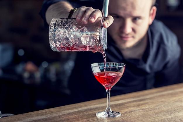 Barmann in der kneipe oder im restaurant, die ein cocktailgetränk zubereitet.