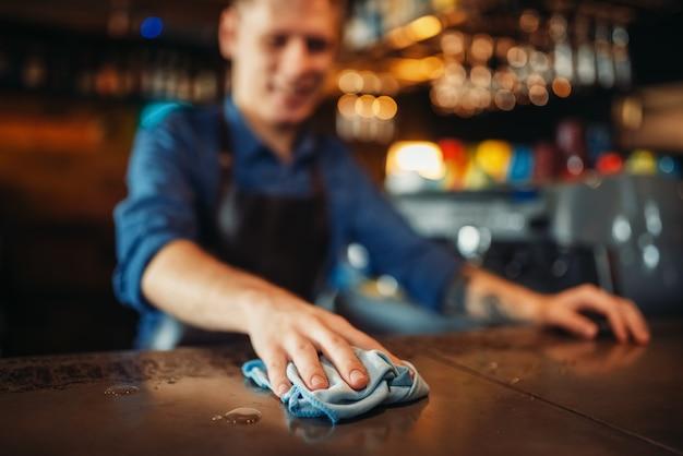 Barmann in schürze reinigt bartheke nach der party