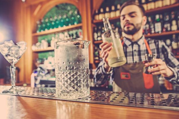 Barmann macht einen alkoholischen cocktail an der theke an der bar