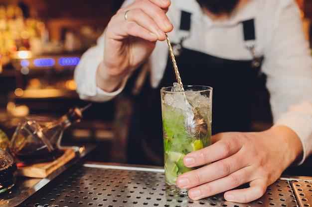 Barmann macht einen cocktail an der bar im restaurant.