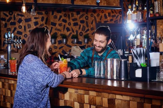 Barmann macht einen cocktail für kunden an der theke