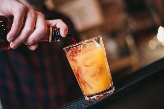 Barmann macht tequila sunrise cocktail im nachtclub. selektiver fokus auf glas.