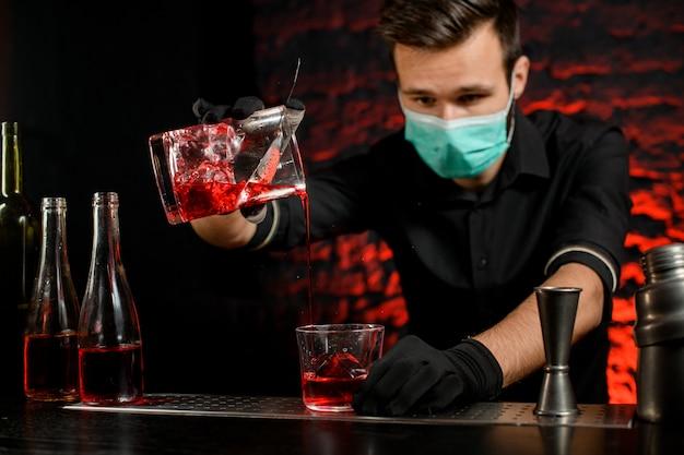 Barmann mit maske gießt meisterhaft kalten cocktail in glas