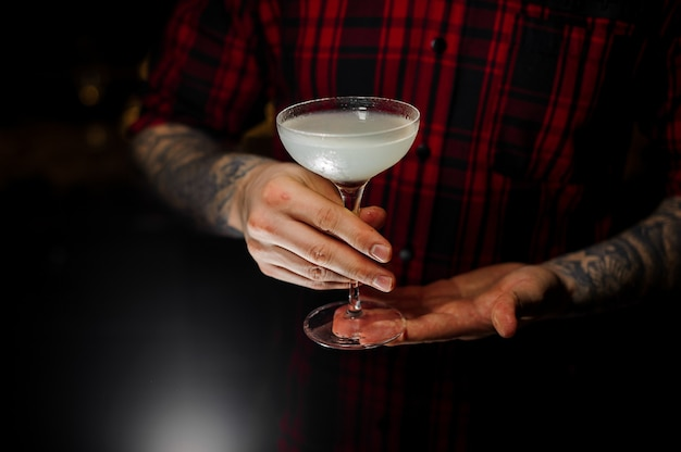 Barmann mit tätowierungen, die ein glas des frischen süß-sauren cocktails im dunklen hintergrund halten