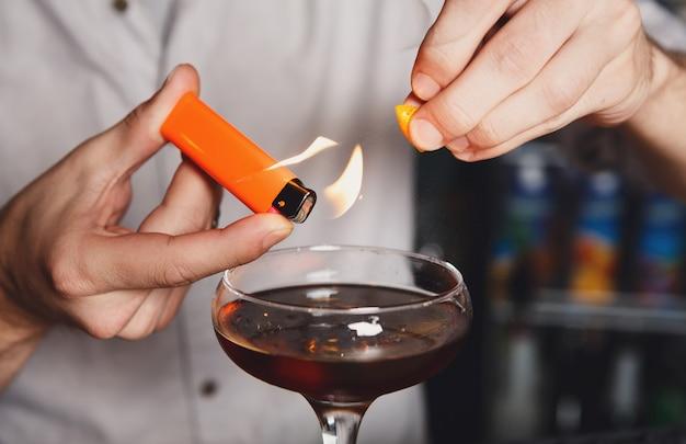 Barmannhände, die flammendes cocktail machen