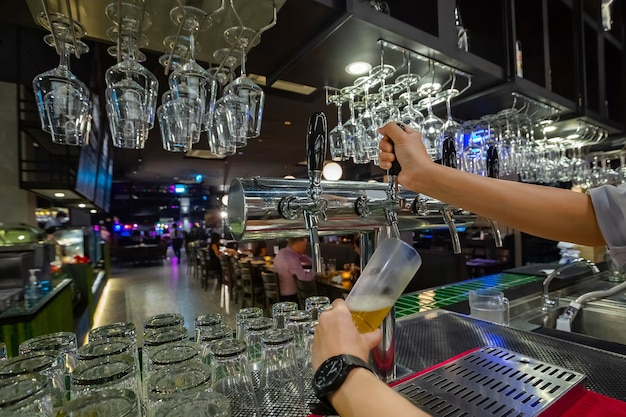 Barmannhände gießen ein lagerbier in ein glas