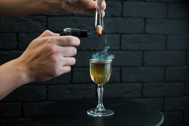 Barmannmann macht heißen alkoholischen feuercocktail auf einem holztisch in einer bar nahe schwarzer backsteinmauer. der barkeeper zündet ein feuerzeug über einem glas an.