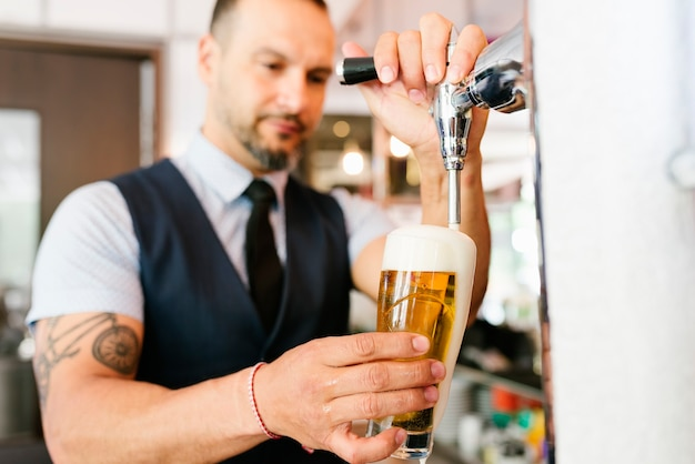 Barmannshand am bierhahn, der ein gezapftes lagerbier gießt, das in einer kneipe dient