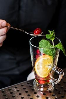 Barmixer bereitet fruchttee mit moosbeeren in einem glas zu