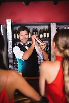 Barmixer, der cocktail im mixbecher am barzähler rüttelt