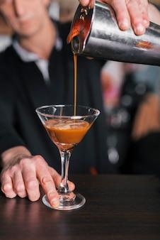 Barmixer, der ein auffrischungscocktail zubereitet