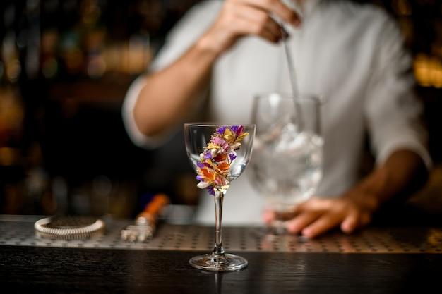 Barmixer, der ein cocktail mit einem löffel im fokusvordergrund der blume rührt, verzierte glas